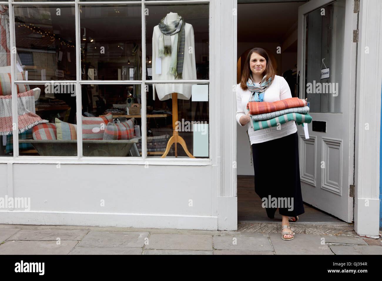 Propriétaire de boutique de tissu holding porte Photo Stock
