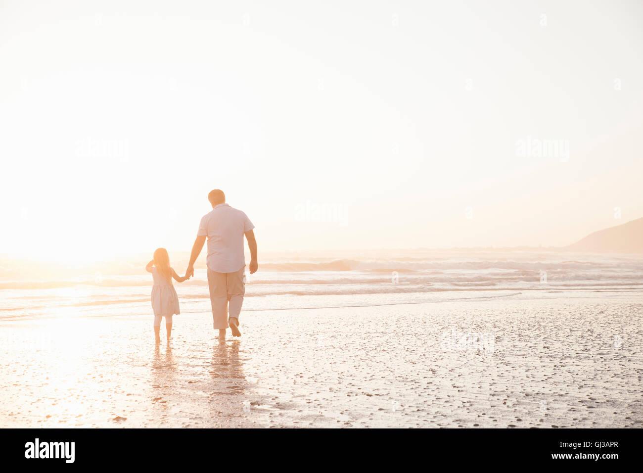 Père et fille se tenant la main en pagayant ocean Photo Stock