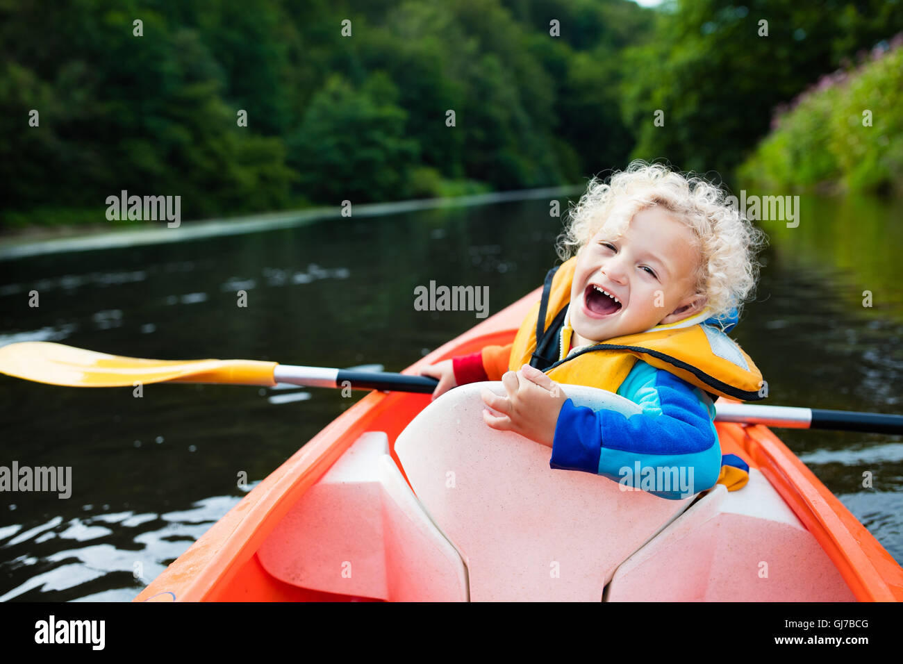 Happy kid bénéficiant en kayak sur la belle rivière. Peu curly bébé garçon kayak sur Photo Stock