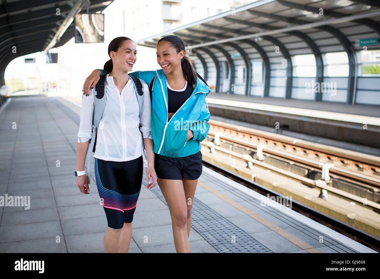 Parution du modèle. Deux jeunes femmes en tenue de sport sur un quai de gare. Photo Stock