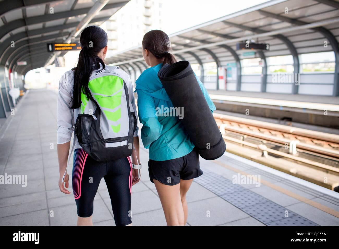 Parution du modèle. Deux jeunes femmes avec des équipements sportifs sur un quai de gare. Photo Stock