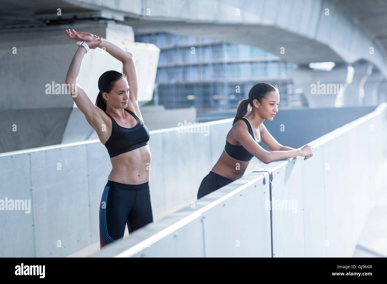 Parution du modèle. Young woman stretching, ami leaning on wall. Photo Stock