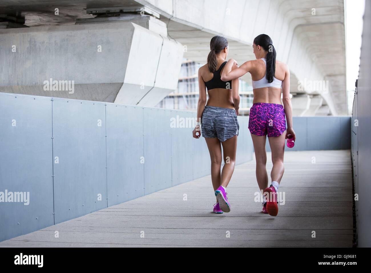 Parution du modèle. Deux jeunes femmes en vêtements sports marche loin. Photo Stock