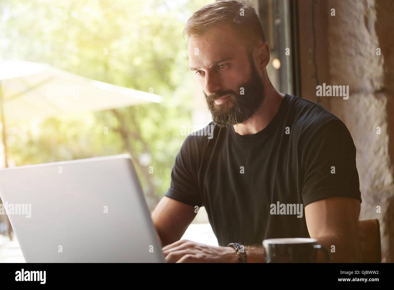 Homme barbu vêtu de noir concentré de travail Table bois portable Tshirt Urban Cafe.Jeune Manager Portable Photo Stock