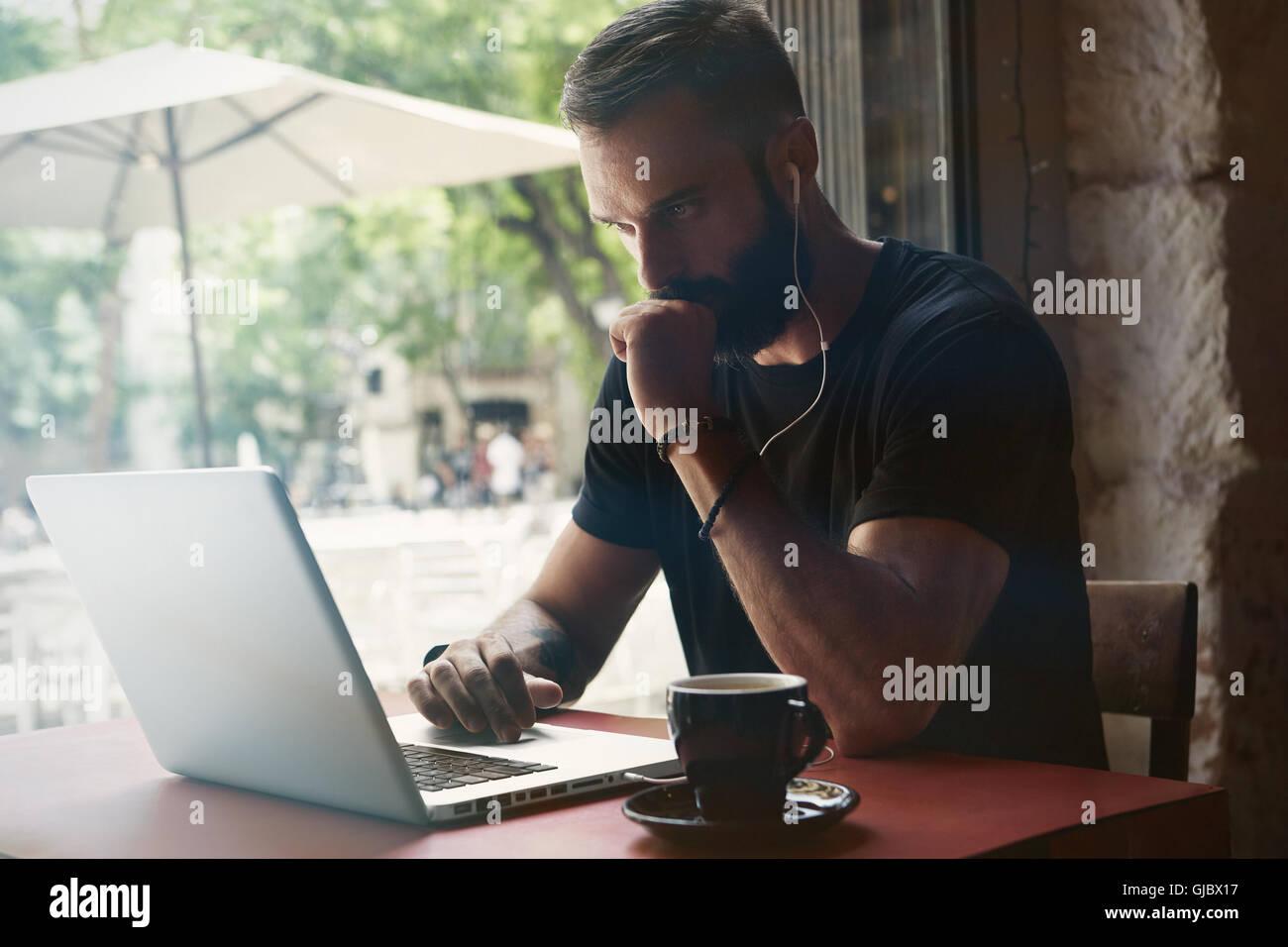 Jeune homme barbu concentré Tshirt vêtu de noir pour ordinateur portable de travail Urban Cafe.homme assis Photo Stock