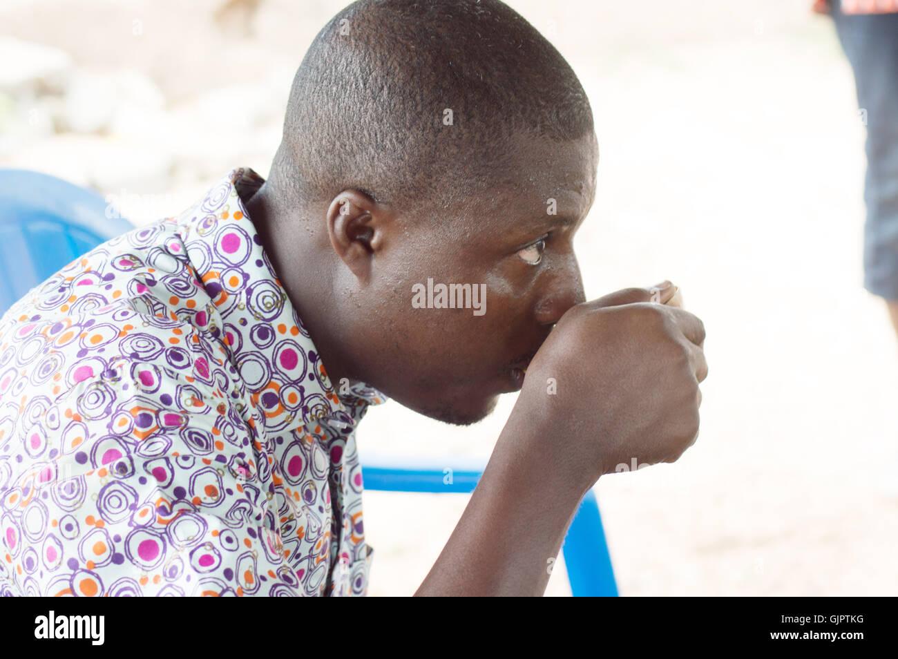 Avec une tasse traditionnelle à la main , ce jeune homme rafraîchit la gorge par le vin de palme. Photo Stock