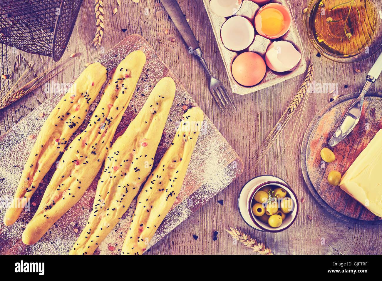 Tons Vintage bâtonnets de pain prêt à cuire, cadre rustique, sur une table en bois. Photo Stock