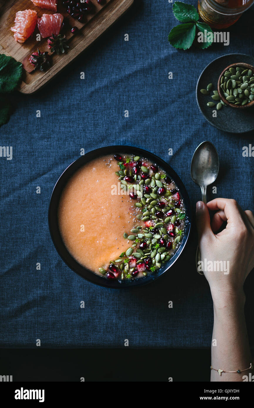 Une femme est sur le point de manger un bol de Smoothie Agrumes cantaloup photographié d la vue supérieure. Photo Stock