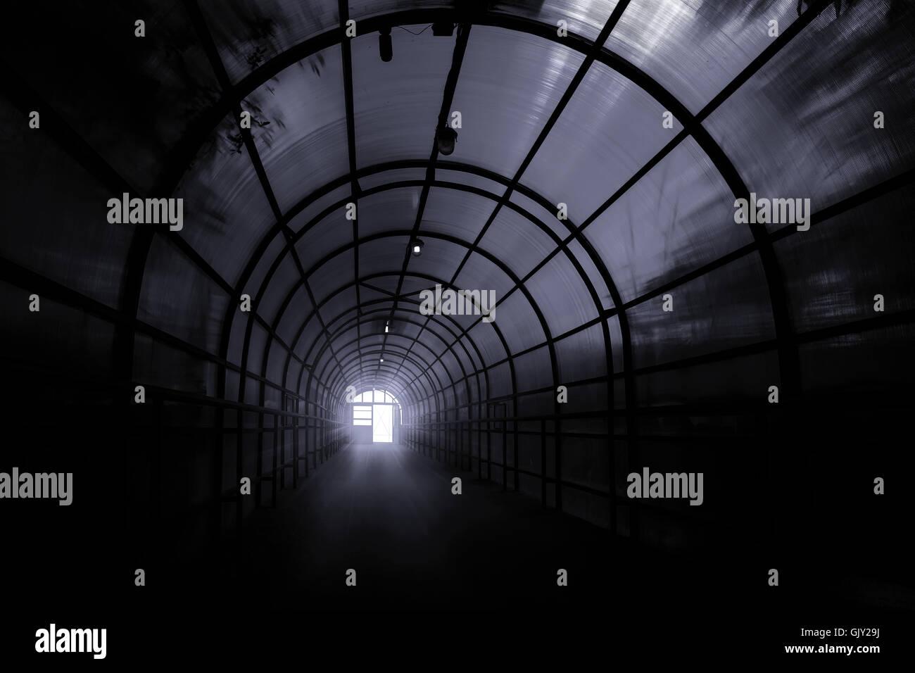 Tunnel sinistre sombre avec des ombres sur les murs et la lumière à la fin de c Photo Stock