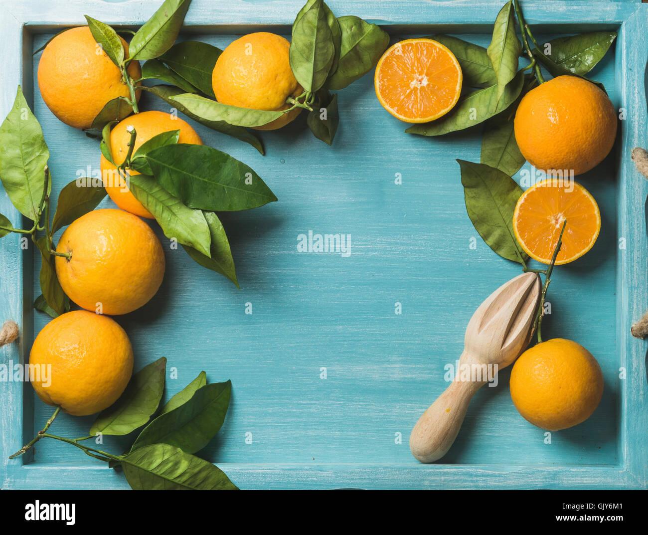 Les oranges fraîches avec des feuilles sur fond de bois peint en bleu, vue du dessus, copiez l'espace, Photo Stock