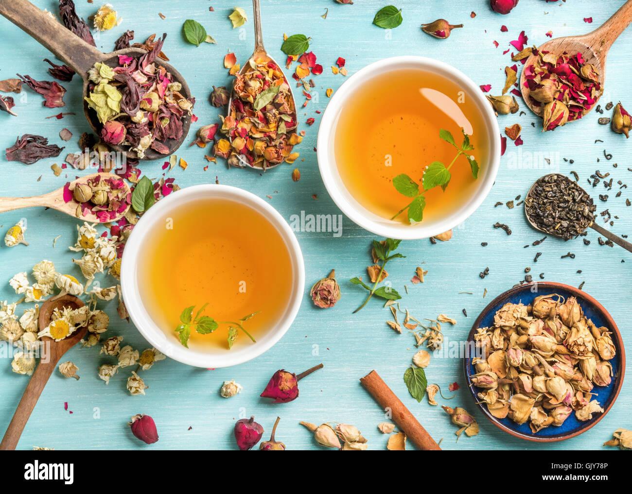 Deux tasses de thé à base de plantes en bonne santé avec la menthe, cannelle, rose et fleurs de camomille Photo Stock