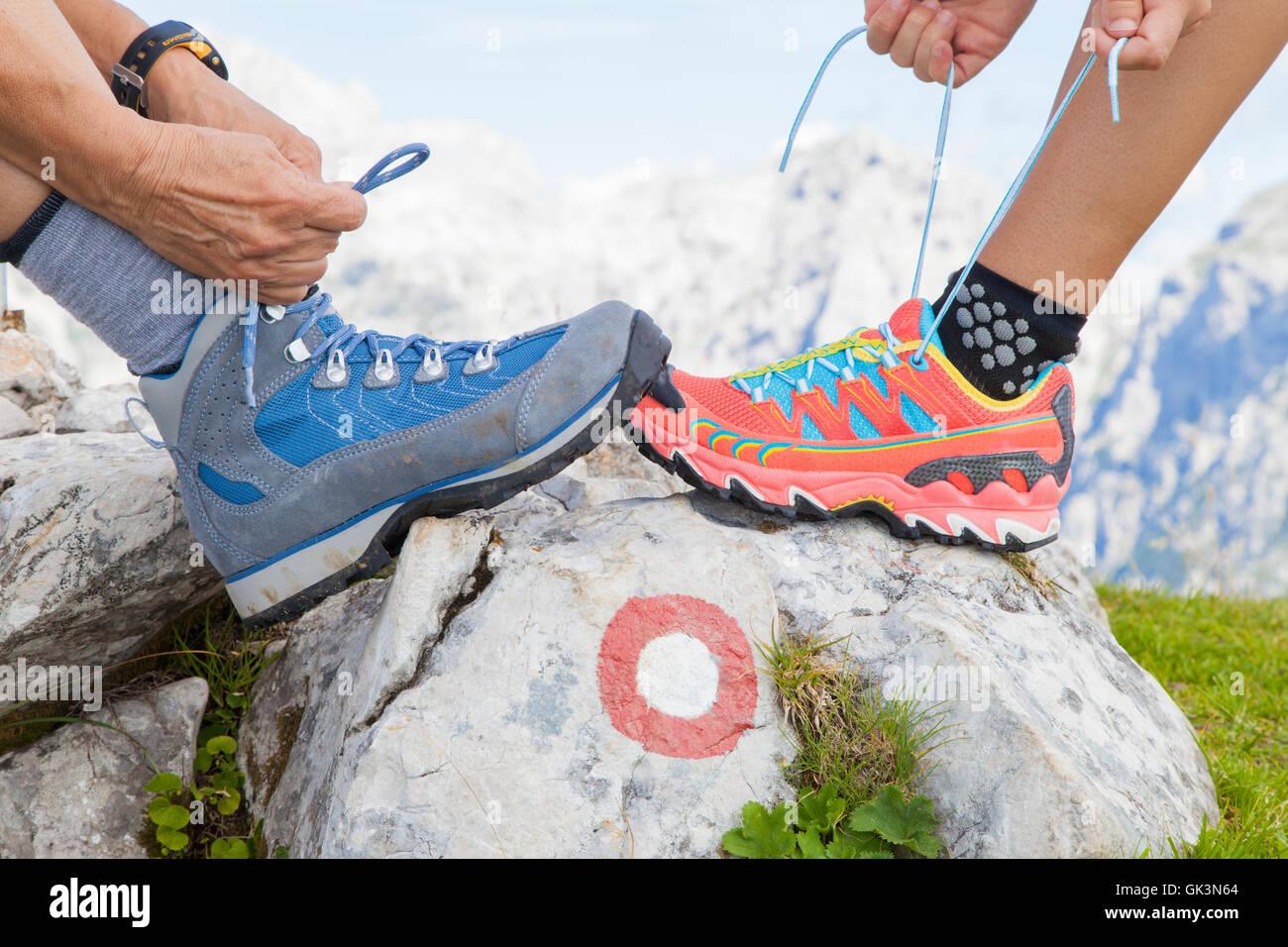 Deux randonneurs attachant lacets, haut dans les montagnes Banque D'Images