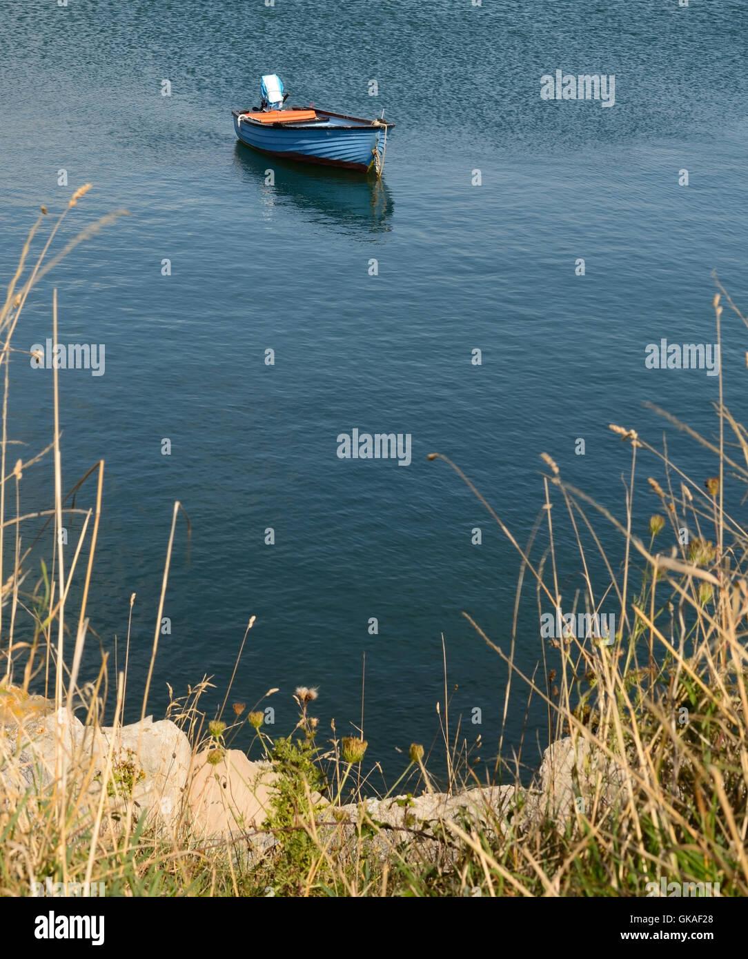 Un petit bateau amarré au large. Photo Stock