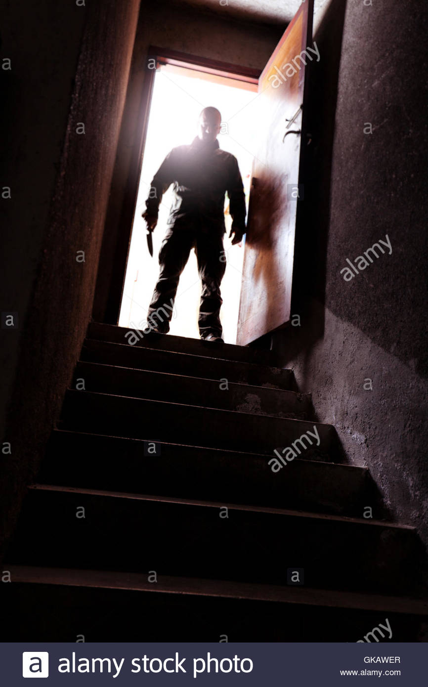 Killer avec couteau et escalier maison souterraine Photo Stock