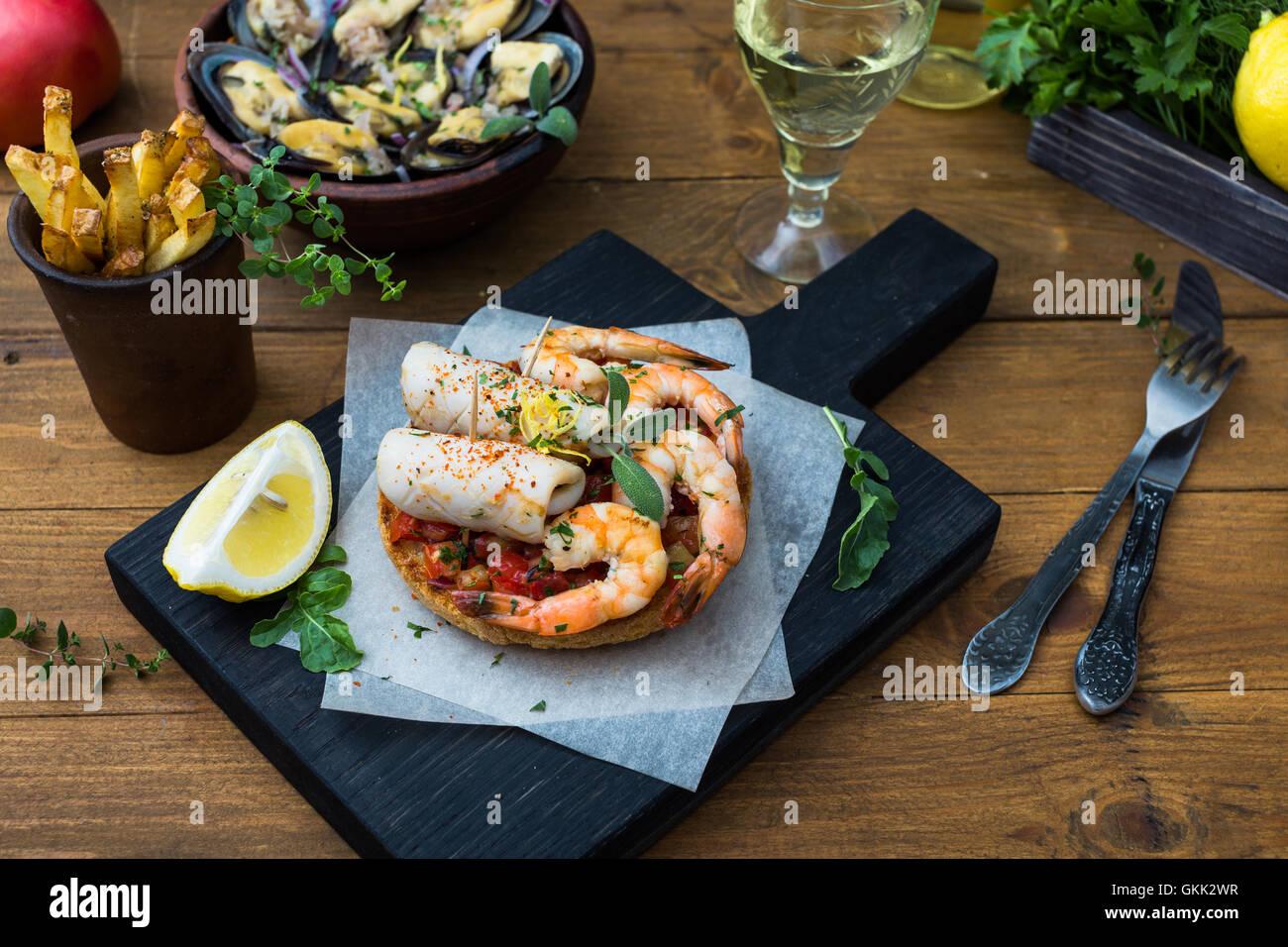 Cuisine italienne. Bruschetta avec les calmars et les crevettes, les tomates et le persil Photo Stock