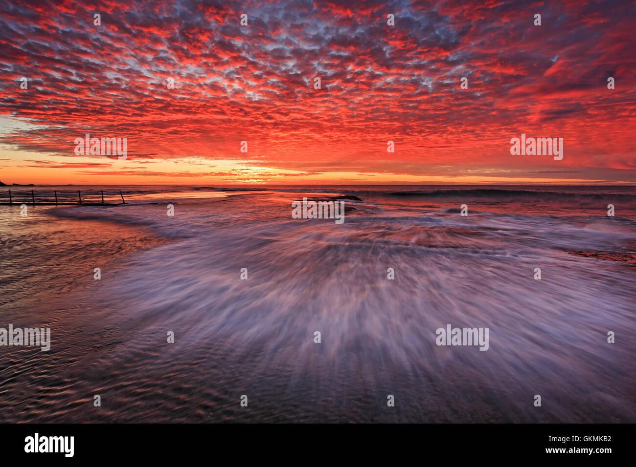 À l'onde rapide trouble heure d'or sur fond de rochers plats autour de la piscine rock Mona Vale beach Photo Stock