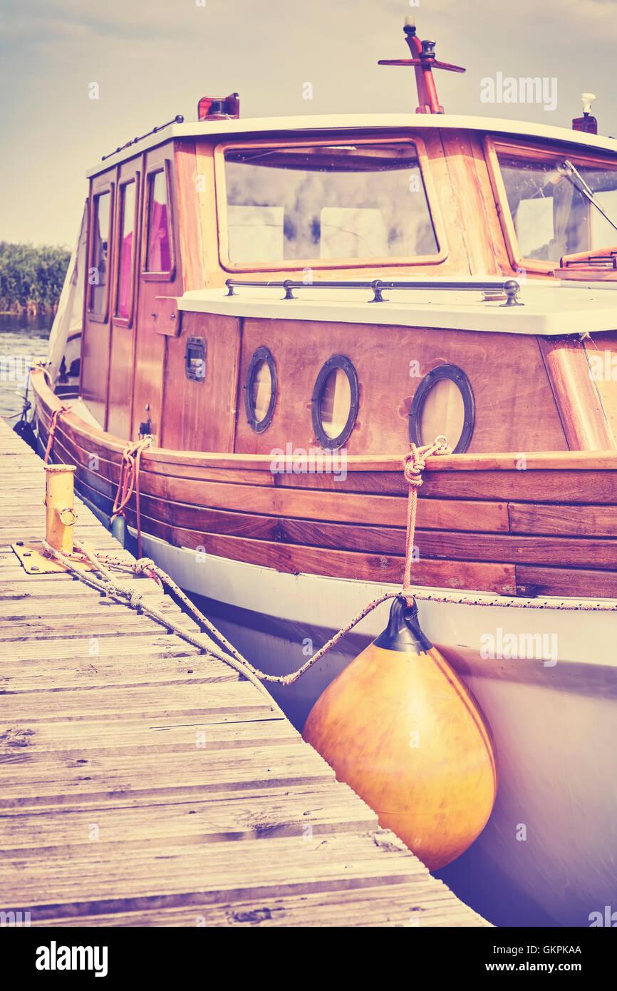 Retro en bois stylisés bateau amarré à un quai à marina. Photo Stock