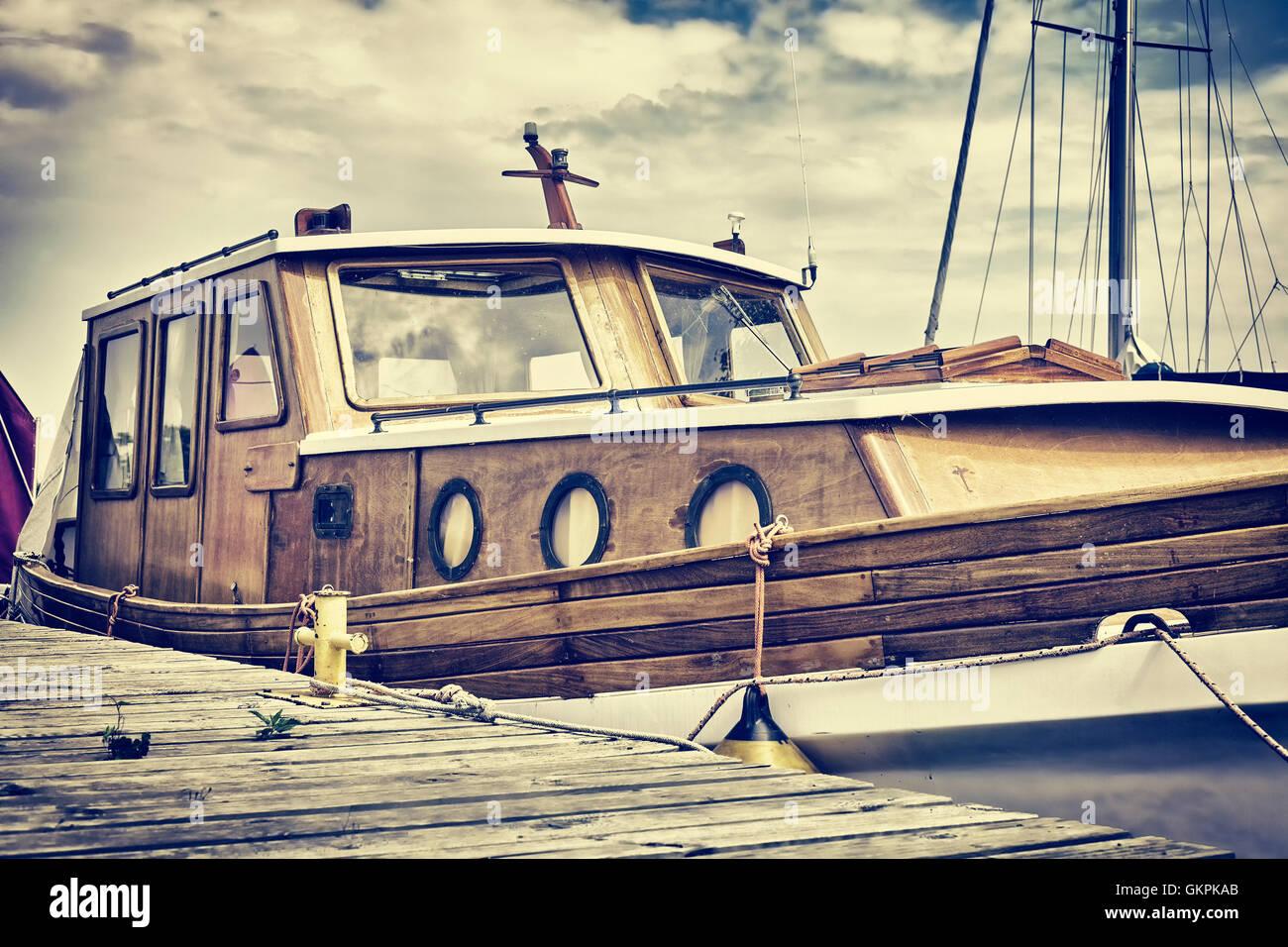 Vintage film ancien bateau en bois aux tons amarrés à un quai de plaisance. Photo Stock