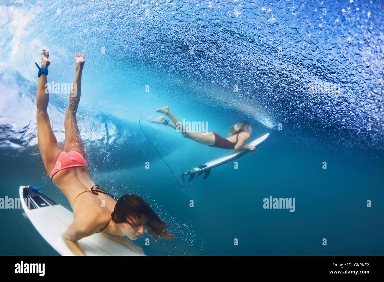 Filles en bikini active en action - surfers avec planche de surf sous-marine Plongée en vertu de briser grand Photo Stock