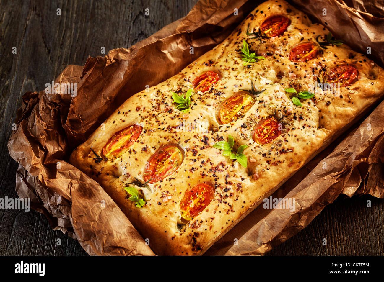 Focaccia italienne fraîchement cuit au four avec des tomates sur une vieille table en bois. Photo Stock