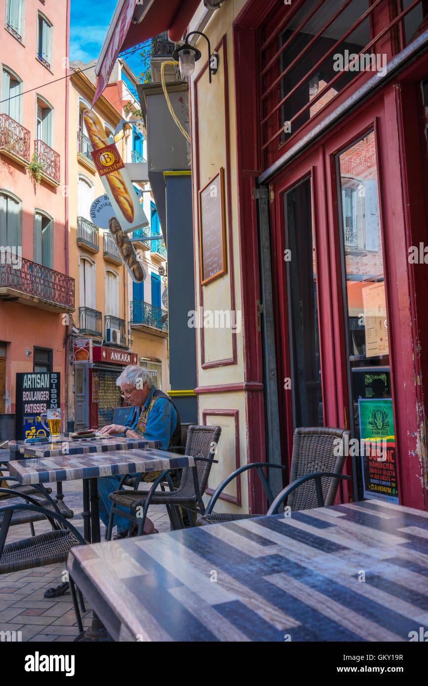 L'homme assis à un café de la rue à Perpignan, France Photo Stock
