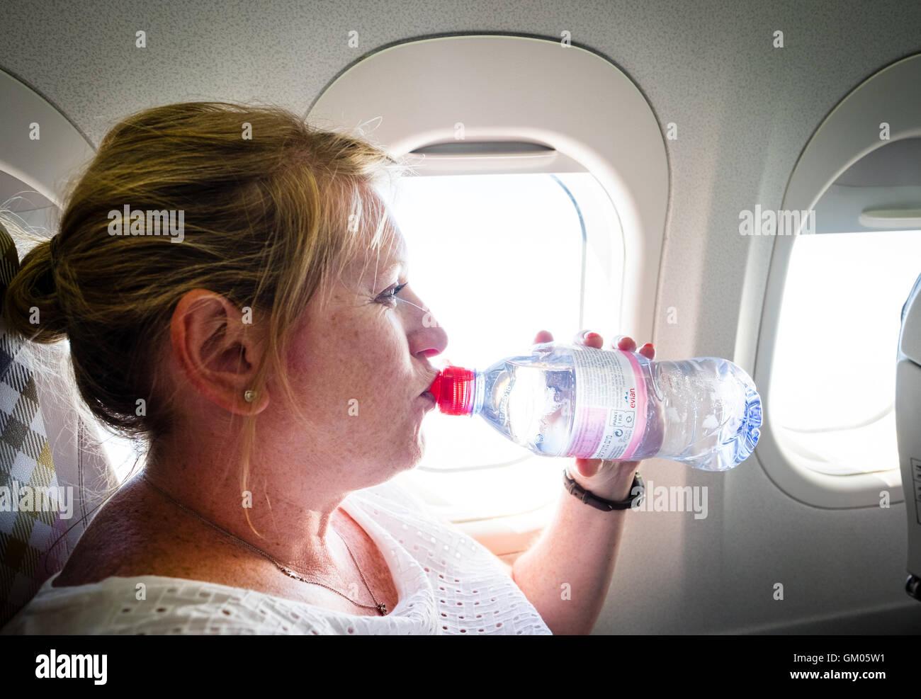 Une femme à boire une bouteille d'eau pour rester hydraté durant un vol sur un avion Photo Stock