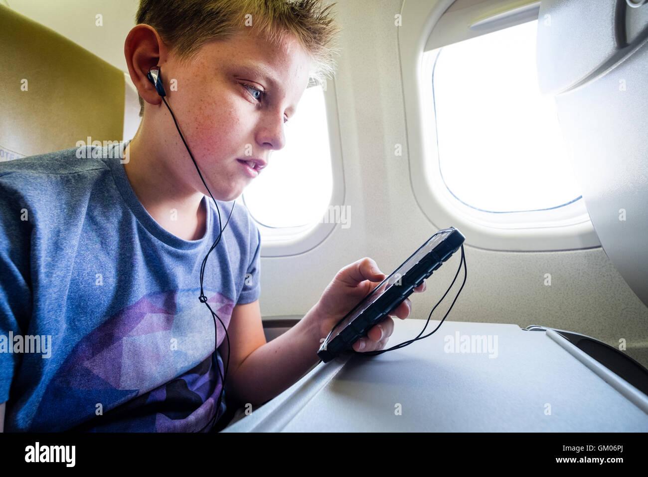 Un adolescent en utilisant son téléphone mobile pendant le vol dans un avion pour écouter de la musique Photo Stock