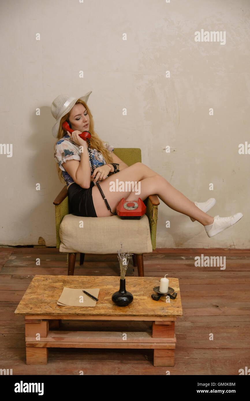 Jolie blonde en white hat est situé sur le vieux fauteuil les jambes croisées et communique par téléphone Banque D'Images