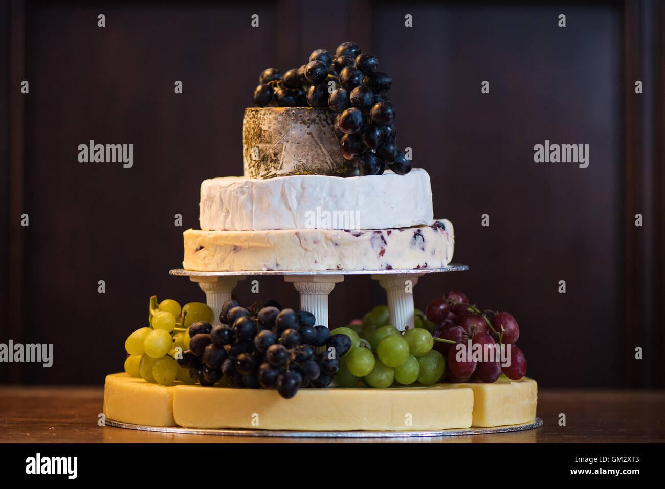 Une pile de fromages avec des raisins formant un gâteau à une réception de mariage Photo Stock