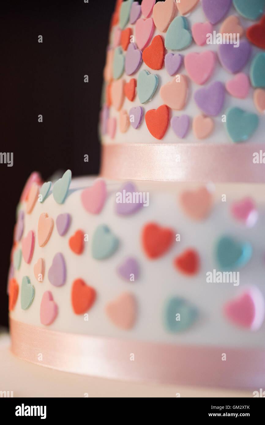 Close up love heart détails sur un gâteau de mariage au cours d'une réception de mariage Photo Stock