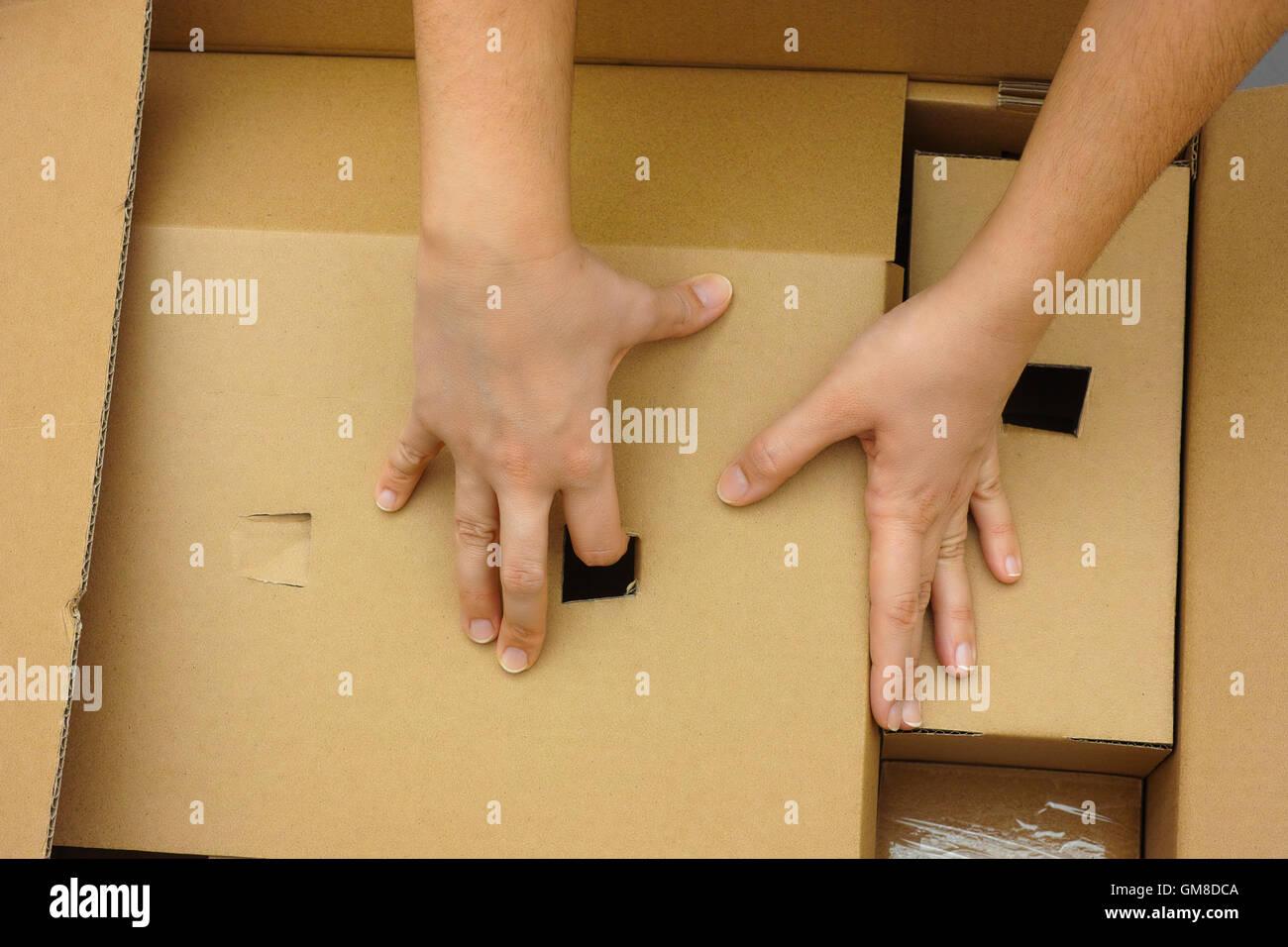 Deux mains femme grand déballage du carton. Photo Stock
