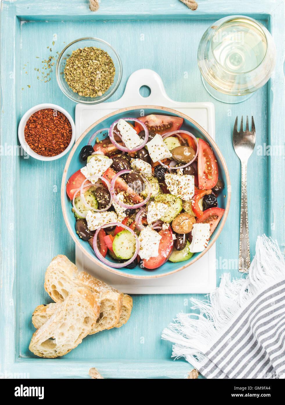 Salade grecque avec du pain, de l'origan, le poivre et un verre de vin Photo Stock
