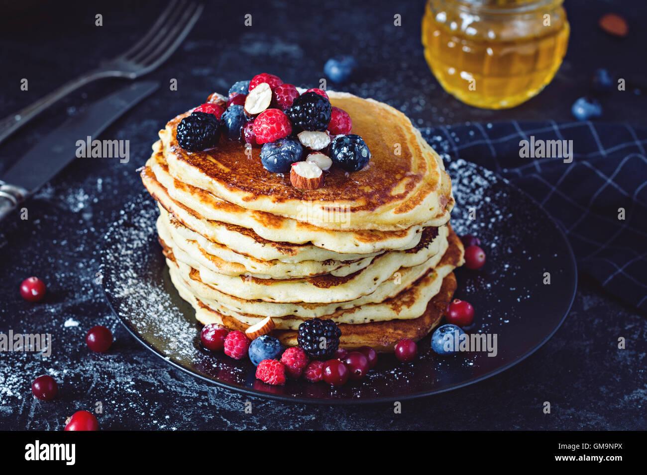 Des crêpes avec les baies fraîches et de miel sur fond ardoise foncé Photo Stock
