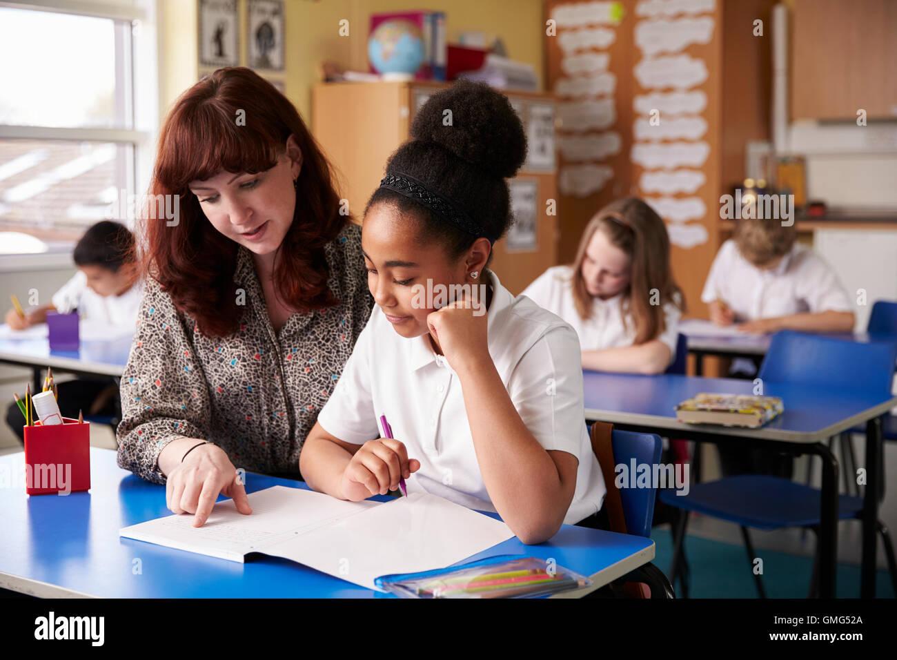 Aider un enseignant du primaire à son bureau d'écolière Photo Stock