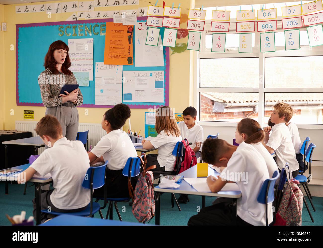 Avec l'ordinateur de l'enseignant en face de la classe de l'école primaire Photo Stock
