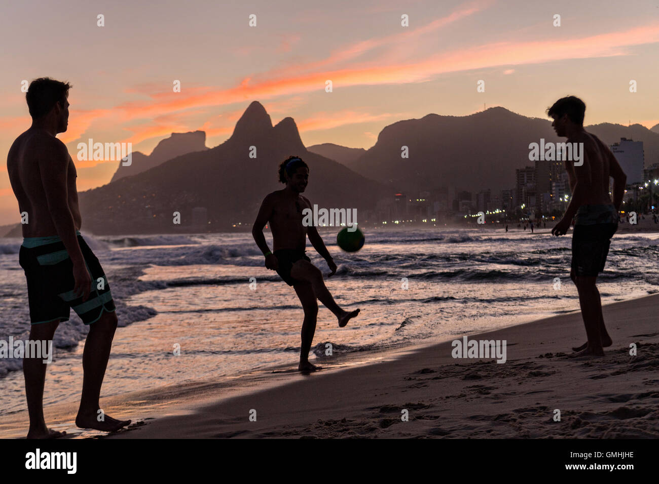 Les jeunes hommes jouent au football sur la plage d'Ipanema silhouetté par le coucher du soleil avec les Photo Stock