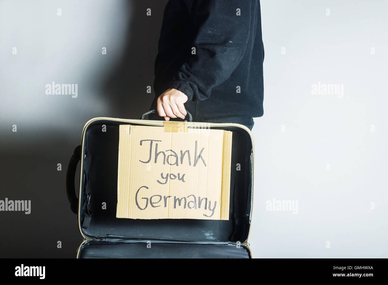 Valise ouverte avec des réfugiés message merci Allemagne sur carton Photo Stock
