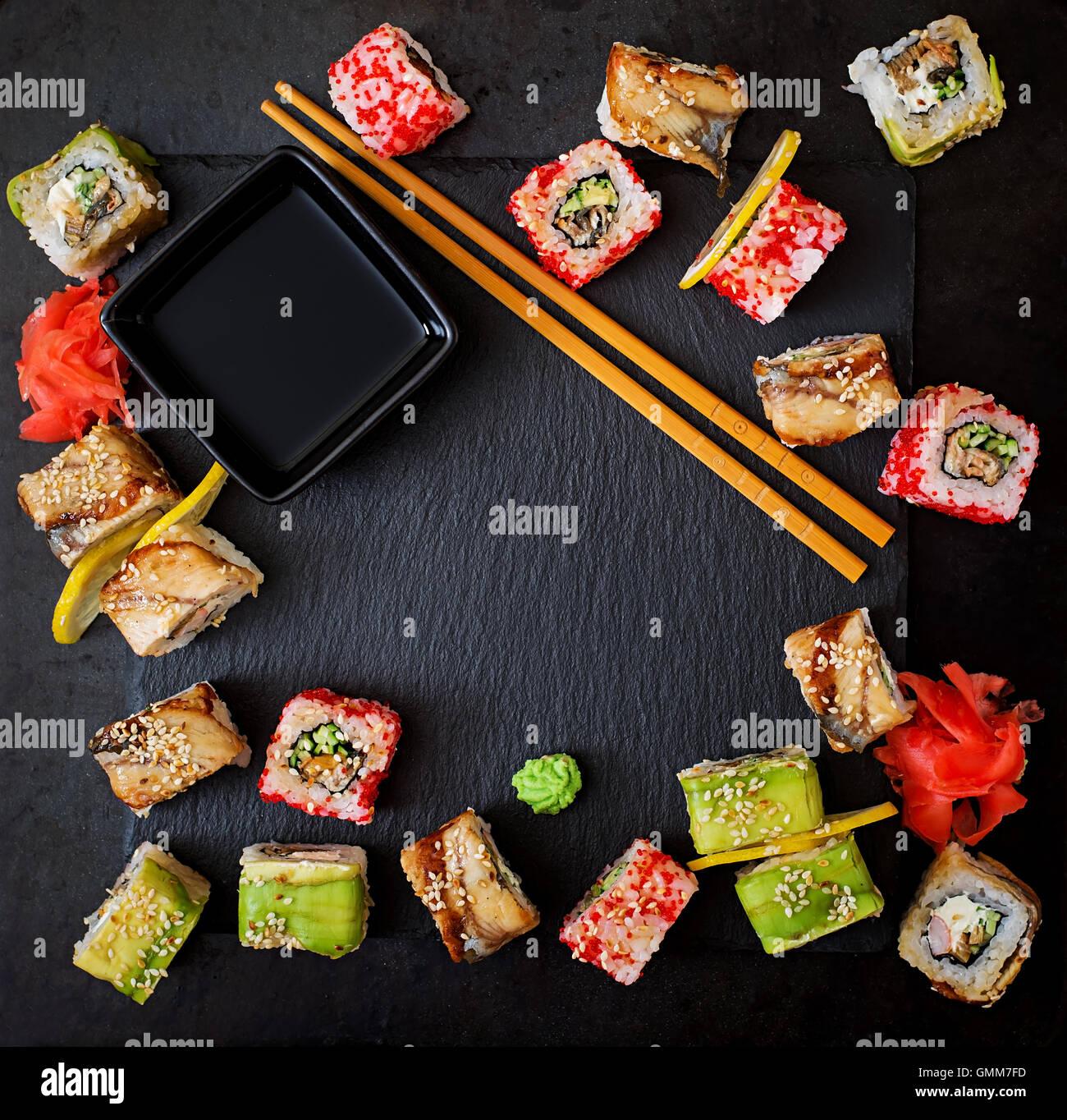 La cuisine japonaise traditionnelle - rouleaux de sushi, et la sauce sur un fond noir. Vue d'en haut Photo Stock