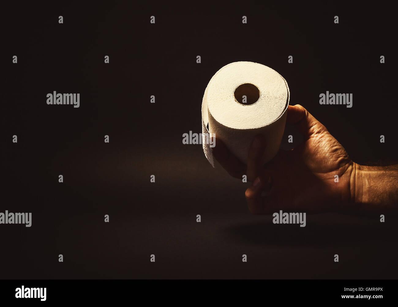 Composition conceptuelle, man's hand holding ou de donner un rouleau de papier de toilette. Banque D'Images