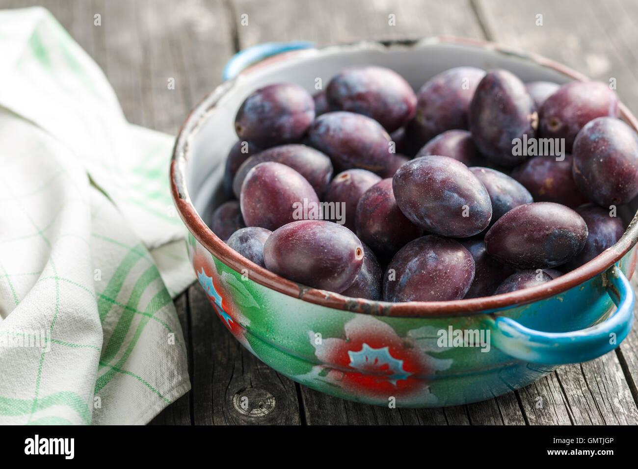 Prunes fraîches du jardin dans un bol sur la vieille table en bois. Photo Stock