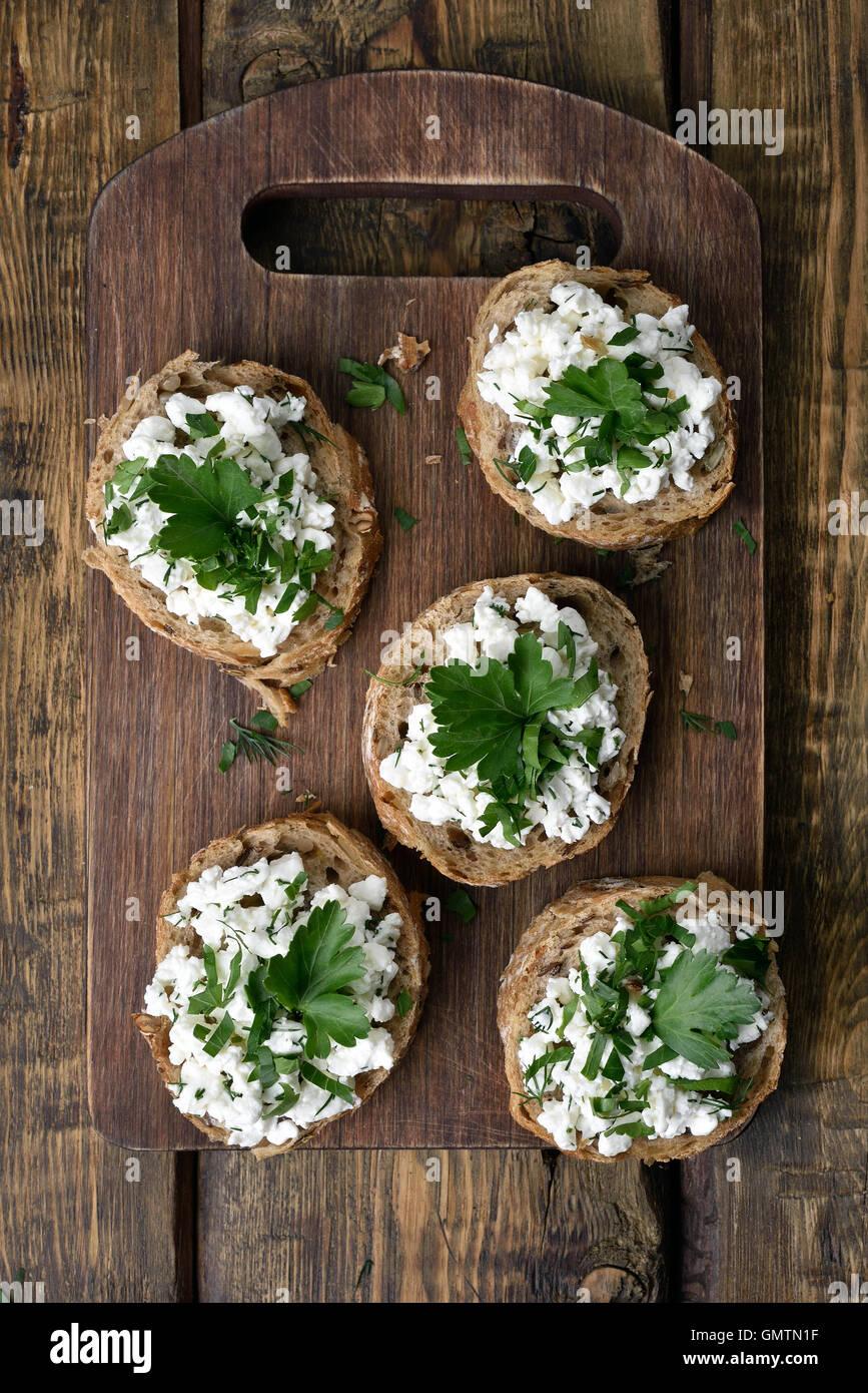 Fromage blanc et herbes vertes sur du pain, des sandwichs sains, vue du dessus Photo Stock