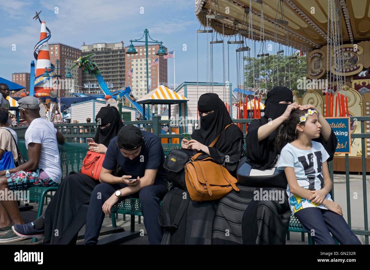 Une famille musulmane avec les femmes en burqas contre au Luna park de Coney Island, Brooklyn, New York. Photo Stock