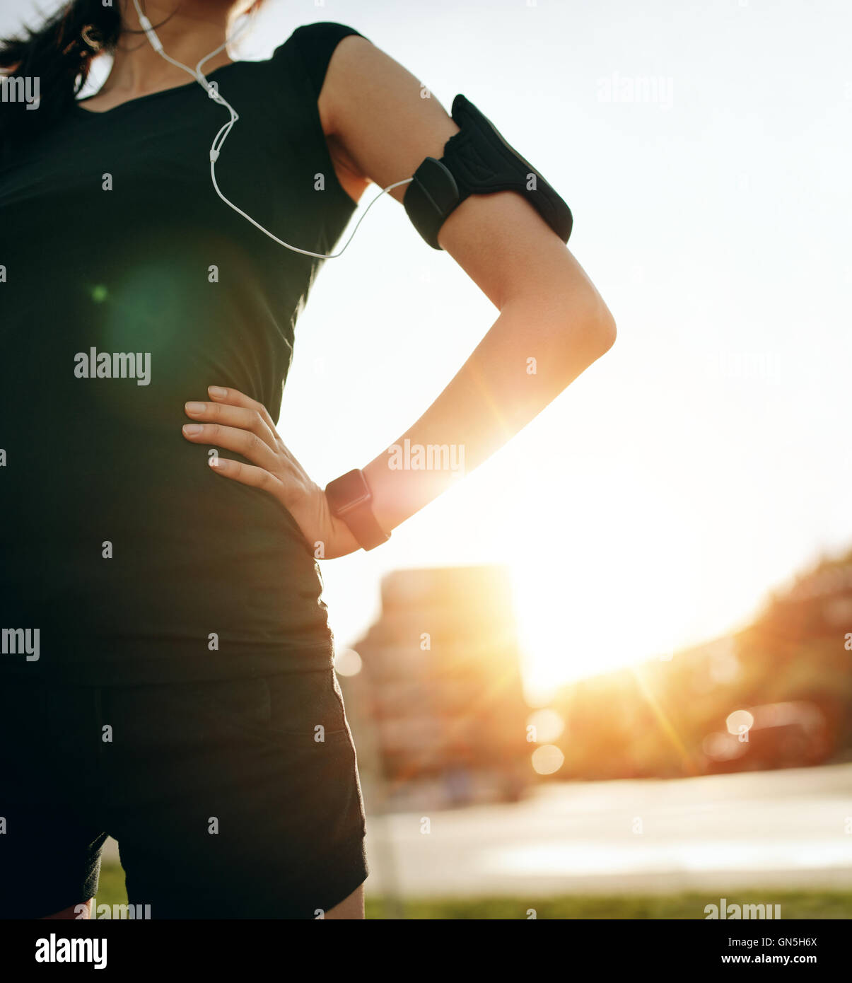 Cropped shot of fit woman standing outdoors avec ses mains sur les hanches. Coureuse portant des smartwatch device Photo Stock