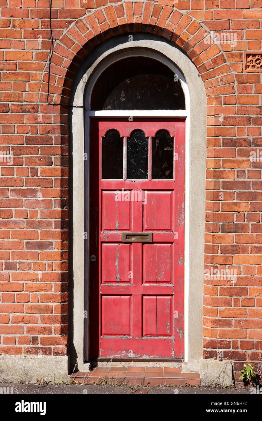 Peinture rouge peeling dans une porte en bois dans une porte voûtée de demeure victorienne en briques Photo Stock