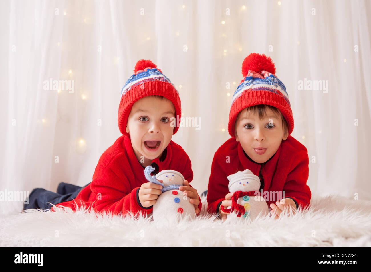 Les enfants, les garçons doux frère, jouant avec des bonhommes de neige à la maison, les lumières Photo Stock