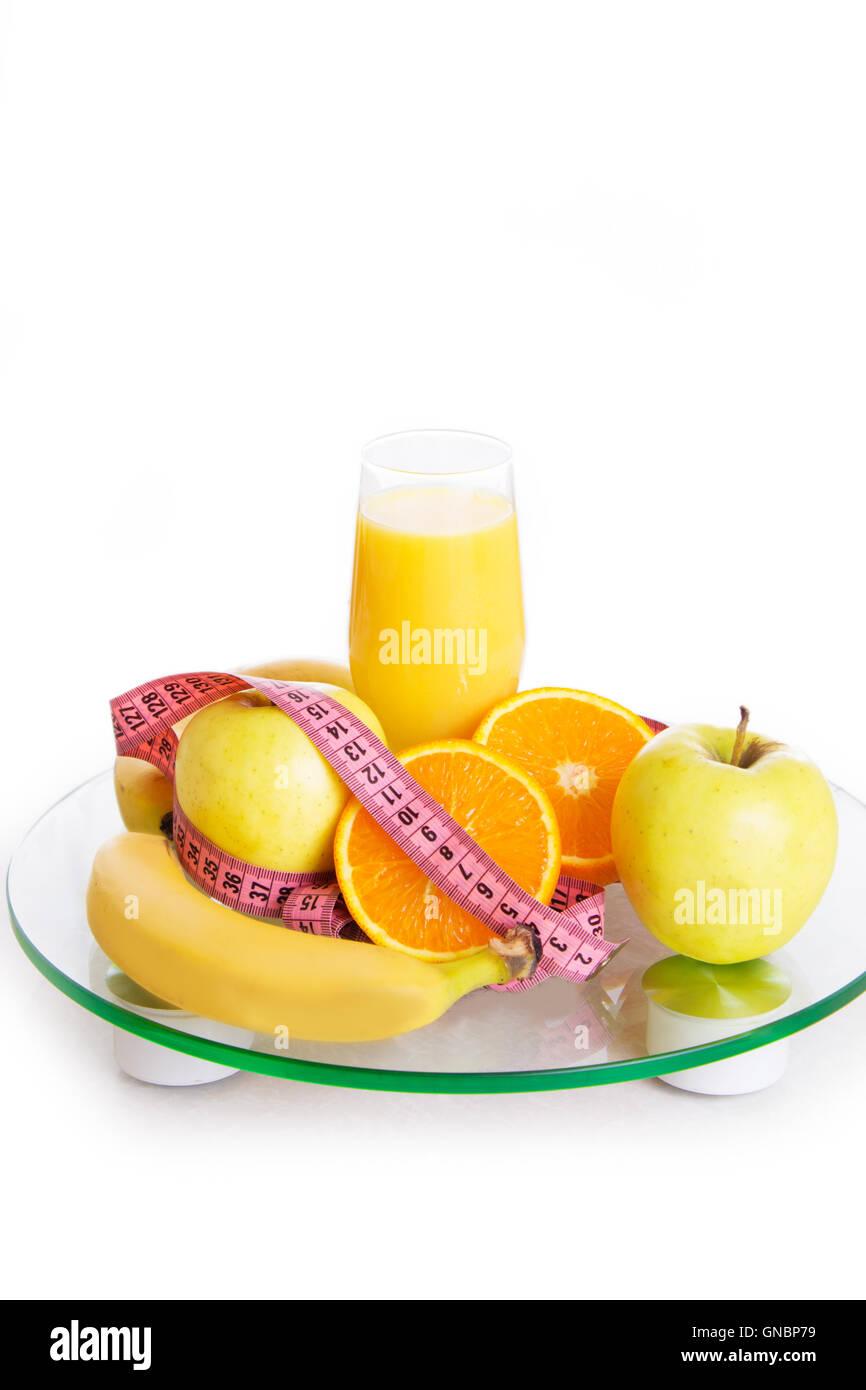 Quelques fruits, jus et mesurer sur des échelles de bande Photo Stock