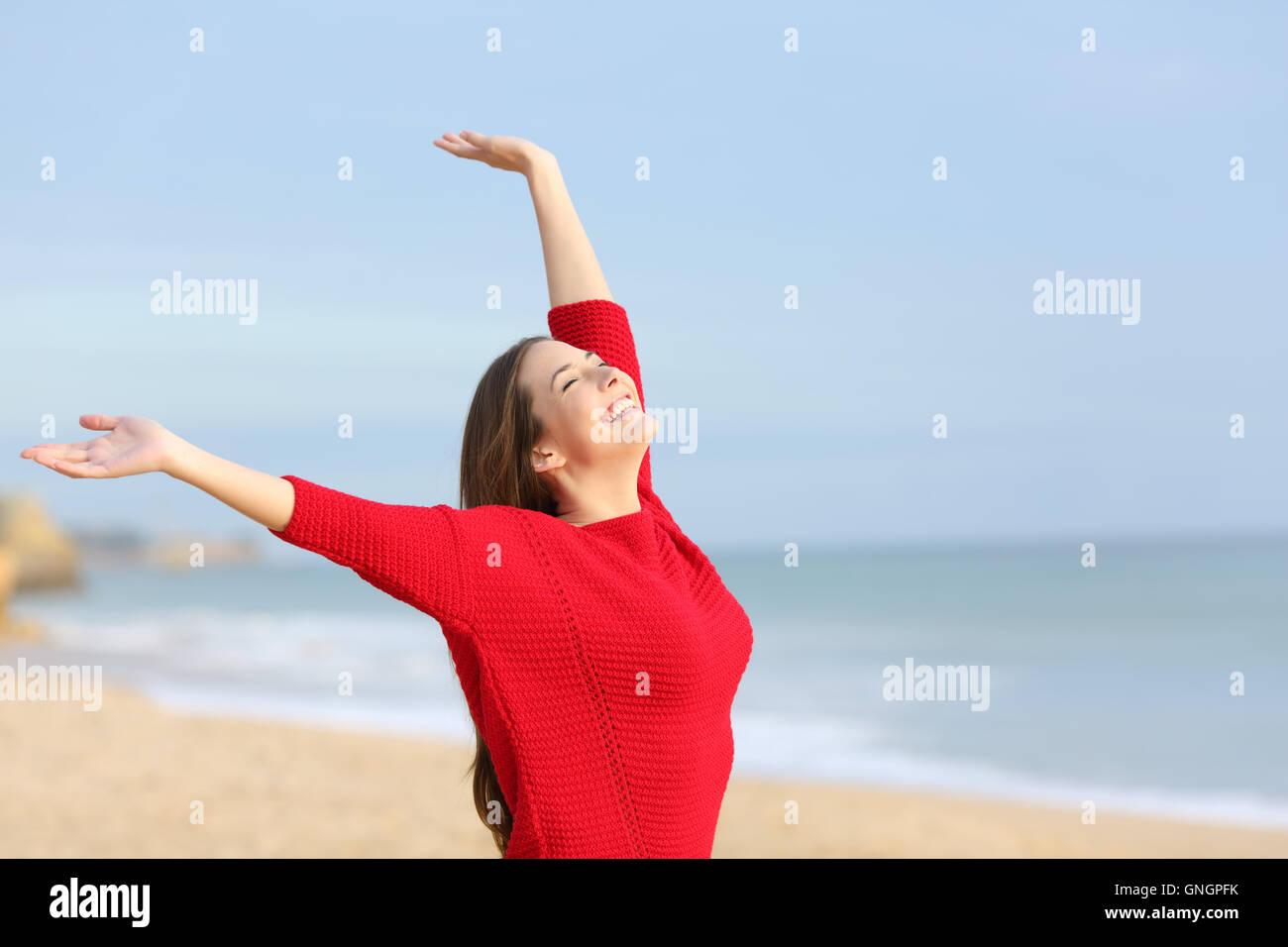 Portrait d'une femme joyeuse heureux excité et raising arms portant un chandail rouge à la plage dans un matin ensoleillé Banque D'Images