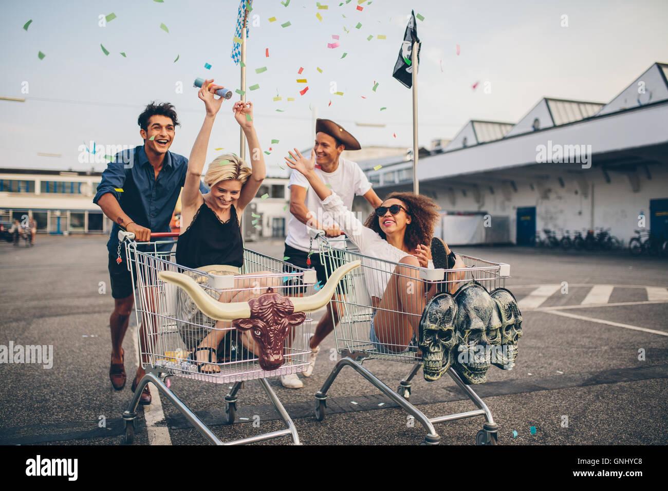 Jeunes amis s'amusant sur un chariot. Les jeunes multiethniques racing sur panier. Photo Stock