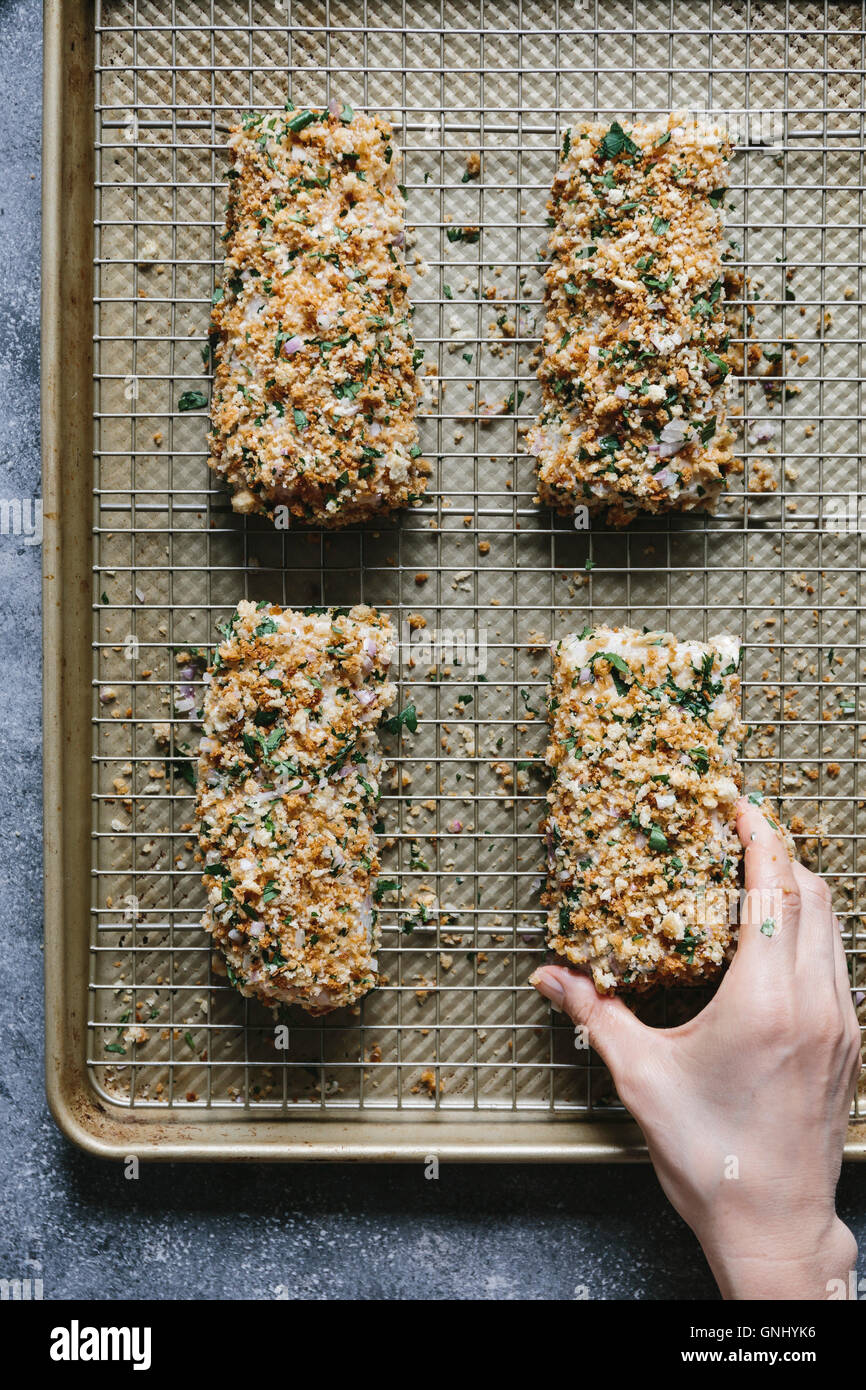 Étape 4/4 Une femme est de placer les filets de poisson enrobé de chapelure sur une plaque de cuisson. Photo Stock