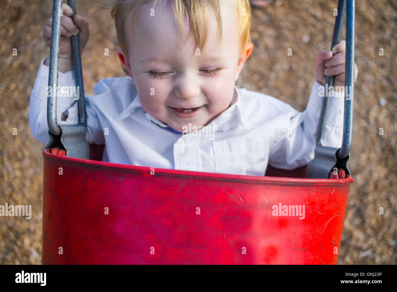 Smiling boy sitting in swing godet Photo Stock